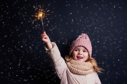 charming little girl in a knitted pink hat holding fireworks on black background in a studio.Cute blonde child with xmas dream.Happy kid enjoy the fire sparks. new year holidays eve of Christmas wish
