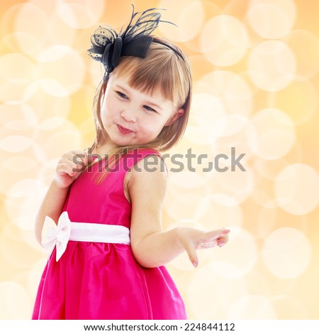 Charming little girl in a pink dress with a white bow. Happiness, winter holidays, new year, and childhood.