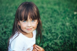 Charming little girl is looking at camera and smiling balck hair and blue eyes