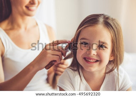 Charming little girl is looking at camera and smiling while her beautiful young mother is combing daughter\'s hair