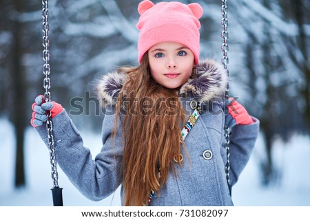 Charming little girl on swing in snowy winter #731082097