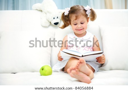 Charming little girl reading book with her toy on white sofa