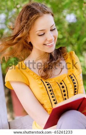 Charming long-haired girl-student reads red book