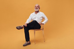 Charming man in white shirt and black pants sitting on orange background. Handsome adult guy in good mood is sitting on chair