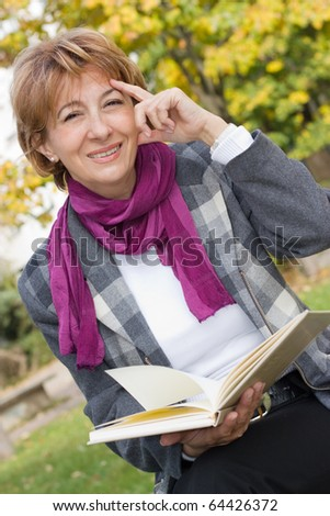 Charming mature businesswoman sitting on the bench reading a book.