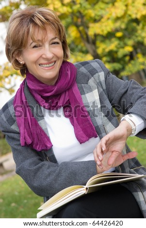 Charming Mature businesswoman sitting on the park bench and checking the  time - stock photo