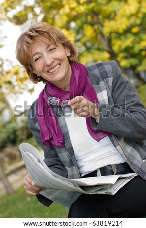 stock photo : Charming Mature businesswoman sitting on the park bench and ...