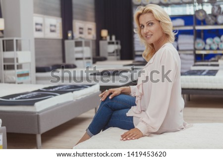 Charming mature woman smiling to the camera sitting on a new orthopedic bed at furniture store, copy space. Happy female customer buying comfortable mattress for healthy sleep
