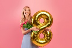 Charming millennial lady with spring flowers and gold balloon celebrating Woman's Day on pink studio background. Gorgeous young blonde holding bunch of tulips and holiday decoration