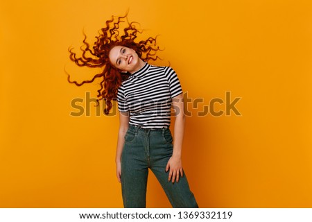 Charming mischievous girl plays hair on orange background. Redhead lady in cropped top and jeans smiles #1369332119