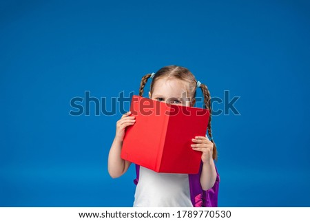 charming mischievous little girl with glasses smiles at the camera and hides behind a book, having fun during school classes on a blue background. Back to school. Photo stock ©