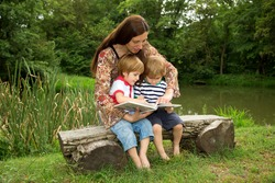 Charming Mother Reading a Book to Her Adorable Little Twin Sons While Sitting Outside  Near Beautiful Lake at Summer