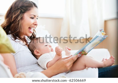 Charming mother showing images in a book to her cute little son at home