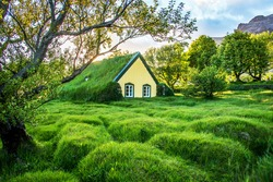 Charming mystical scene with turf roof church with windows and cemetery with small graves in Hof, Skaftafell, Vatnajokull National Park at sunset. Exotic countries.