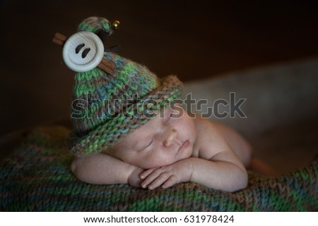 Charming newborn baby in a gnome hat sleeping in a wooden trough on a green knitted rug, rustic style dark
