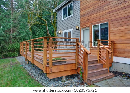 Charming newly renovated home exterior, natural wood and grey siding create a beautiful curb appeal. Detail view of a nice walk out deck with wooden handrails.