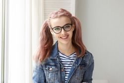 Charming positive 17 year old Caucasian girl wearing her long pink hair in two ponytails relaxing indoors posing against white wall background with copy space for your text or advertising content