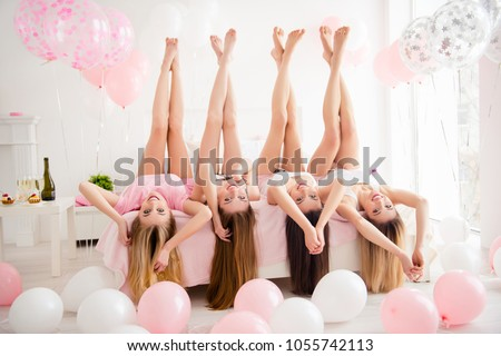 Charming pretty cheerful foolish attractive sexy stylish slender girls lying head over heels on bed with raised crossed legs hands celebrating birthday holiday event looking at camera  sleepover party