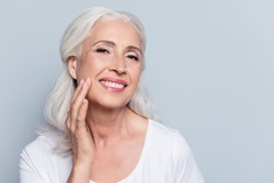 Charming, pretty, old woman touching her perfect soft face skin with fingers, smiling at camera over gray background, using day, night face cream, cosmetology procedures