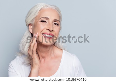 Charming, pretty, old woman touching her perfect soft face skin with fingers, smiling at camera over gray background, using day, night face cream, cosmetology procedures #1018670410