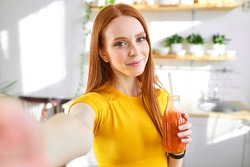 charming redhead food blogger woman drinking juice detox handmade smoothie in kitchen at home