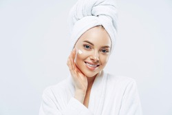 Charming relaxed beauty woman applies face cream, cares about complexion, touches cheek with hand, smiles gently at camera, dressed in bath robe, wrapped towel on washed hair, isolated on white