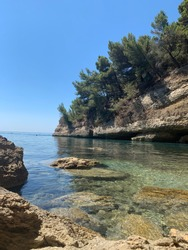 Charming rocky beach on the Adriatic. The purest clear sea. Pebble seabed. Idyllic summer picture. Calm crystalline water. Pine forest. Sea stones. Picturesque cliff. Scenic rocks.Mediterranean nature