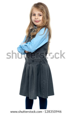 Charming schoolgirl standing sideways with her arms folded.