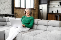 Charming senior elderly woman spends leisure time in networks on the computer, texting messages, watching movies. The mature lady works remotely with a laptop sitting on the sofa in cozy living room