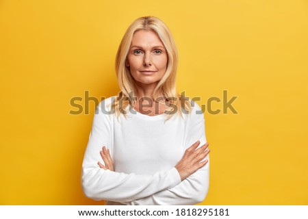 Charming serious middle aged blonde woman stands crossed hands indoor looks directly at camera being confident in future wears casual white jumper poses determined against yellow background. Сток-фото ©