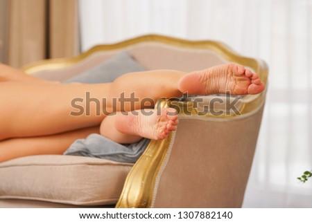charming slender girl lying on the sofa in lingerie with barefoot feet #1307882140