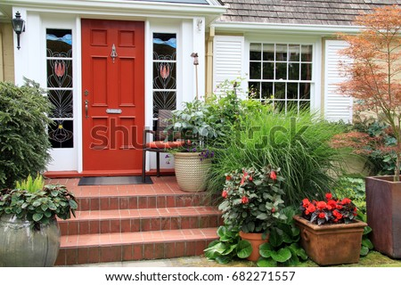 Charming small home with red front door and summer garden containers filled with annual flowers. Photo taken from the public sidewalk.  #682271557
