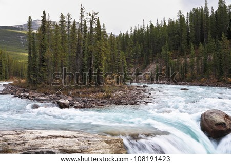 Charming small islet in falls of the mountain river Banff. Early autumn in the Rocky Mountains of Canada