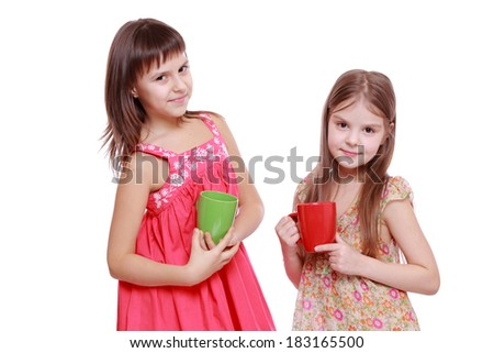 Charming smiley little girls with red and green cup