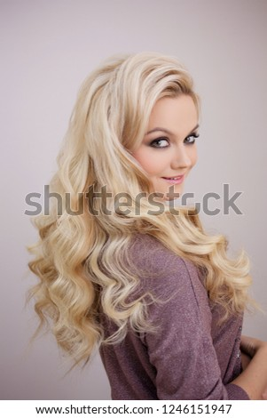 Charming smiling blonde with luxurious blonde curls. Hair beauty and health #1246151947