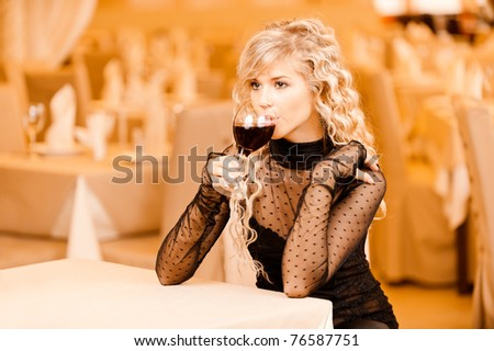 Charming smiling young woman in black clothes drink from red wine glass sits at magnificent restaurant.