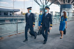 Charming stewardesses and handsome pilots in protective face masks carrying trolley bags at airport