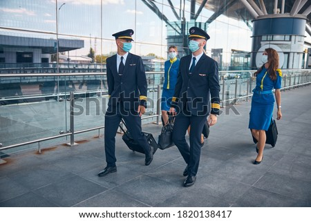 Charming stewardesses and handsome pilots in protective face masks carrying trolley bags at airport Foto stock ©