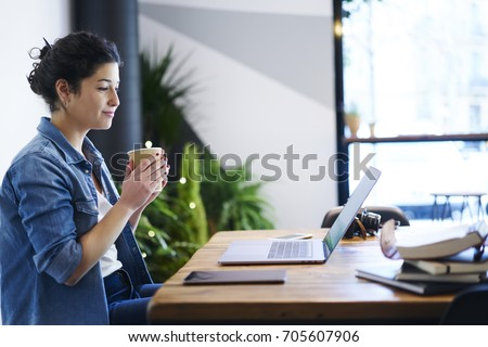 Charming student watching interesting webinar on computer while sitting indoors with coffee in hands.Attractive female enjoying beverage during reading news on laptop device via high speed internet #705607906
