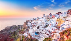Charming sunset view of traditional Greek village Oia on Santorini island in Greece. Santorini is iconic travel destination in Greece, famous of its sunsets and traditional white and blue architecture