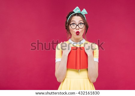 Charming surprised pinup girl in glasses standing and holding red book over pink background
