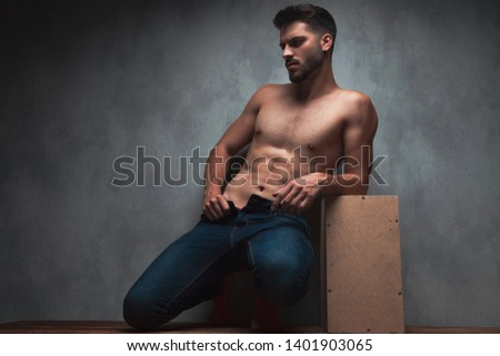 Charming topless  man posing and pulling his jeans while looking to the side, kneeing and leaning on a box, on gray studio background