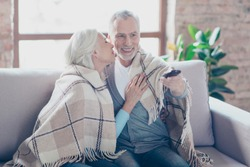 Charming two elderly people are sitting on a couch at home resting relaxing at the weekend talking and watching tv. The man is changing channels and the woman is going to kiss him