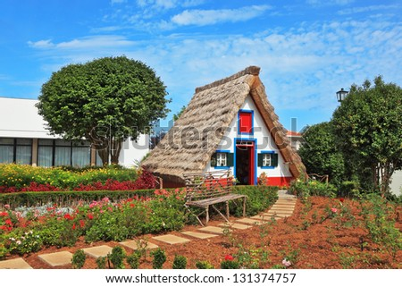 Charming white cottage with a thatched roof and gable small garden with flowers. Picturesque house-museum of the first colonists to Madeira. - stock photo