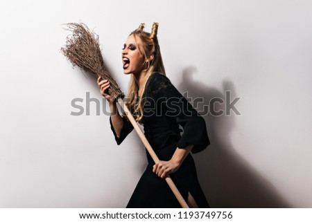 Stock Photo Charming witch in long dress dancing with her broom. Studio shot of gorgeous girl in vampire costume.