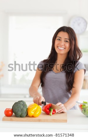Charming woman cooking vegetables while standing in the kitchen