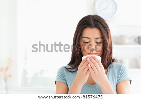 Charming woman enjoying a cup of coffee in the kitchen