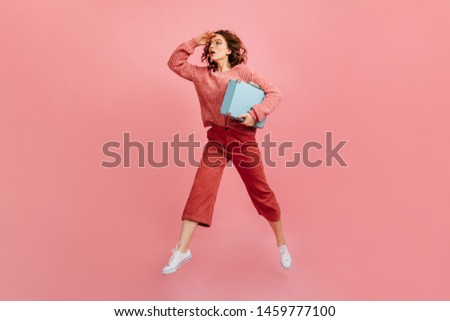 Charming woman holding valise and looking away. Studio shot of worried girl with suitcase.