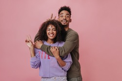 Charming woman in purple sweater and man in brown sweatshirt showing peace signs. Joyful lady and her boyfriend widely smiling on pink background