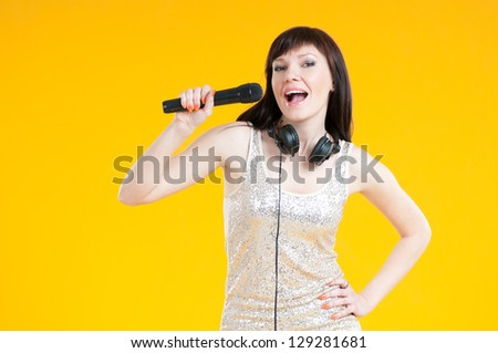 Charming woman singing with a microphone over yellow background